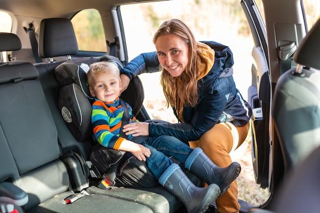 Moeder vastmaken veiligheidsgordel voor haar babyjongen in zijn autostoeltje.