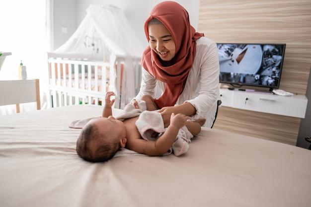 Moeder veegt haar babyjongen af met een handdoek
