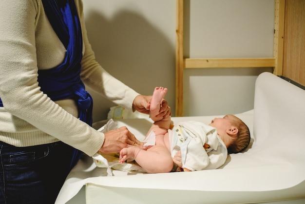 Moeder verandert luier in baby, afvegen met natte doekjes.