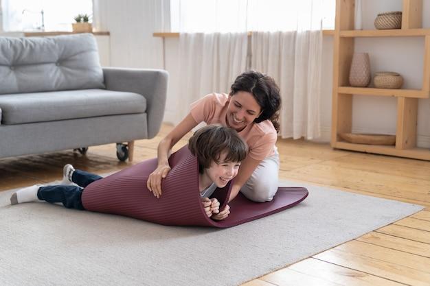 Moeder verpakt glimlachend kind in yogamat spelen met zoon na sportoefening thuis tijdens lockdown
