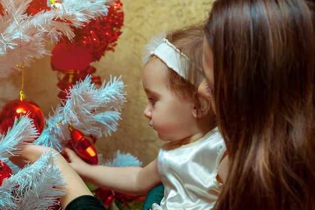 Moeder versiert de kerstboom met haar kleine babymeisje