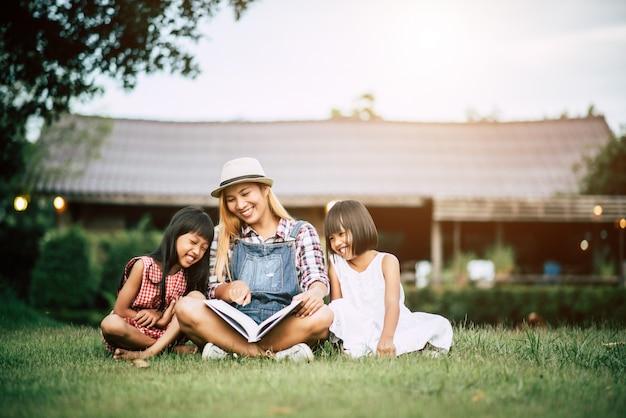 Moeder vertelt een verhaal aan twee dochtertje in de tuin
