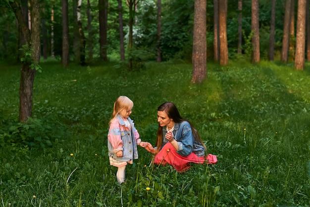 Moeder vertelt haar peuterdochter zittend op het gras over de wereld om haar heen