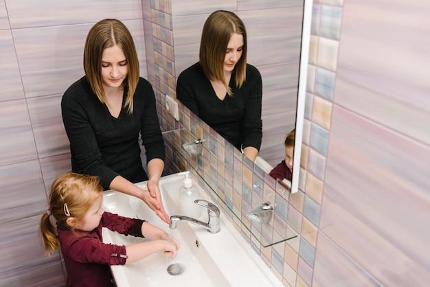 Moeder vertelt het kind hoe ze haar handen goed moet wassen met antibacteriële zeep, warm water over nagels en vingers. handen wassen.