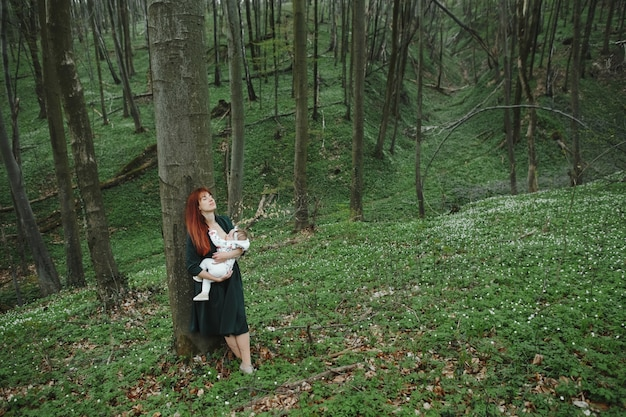 Moeder verzorgt een kleine baby in het bos