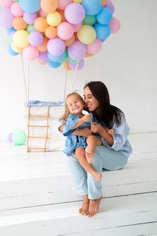 Moeder viert samen met het dochtertje verjaardag. grote stuk speelgoed ballon op de achtergrond.
