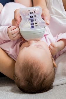 Moeder voedende baby met melkfles in woonkamer