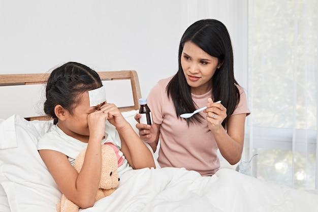 Moeder voedende siroop geneeskunde aan klein meisje