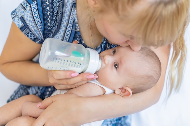 Moeder voedt de baby met een fles.