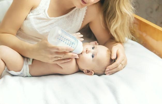 Moeder voedt de baby met een fles