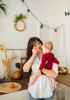 Moeder voedt de wortelpuree van het babymeisje in keuken thuis