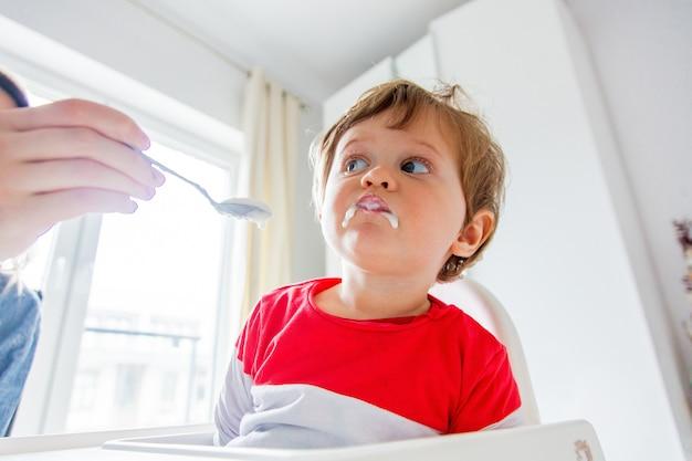 Moeder voedt een kleine peuterjongen met een lepel tijdens de lunch in de kamer.