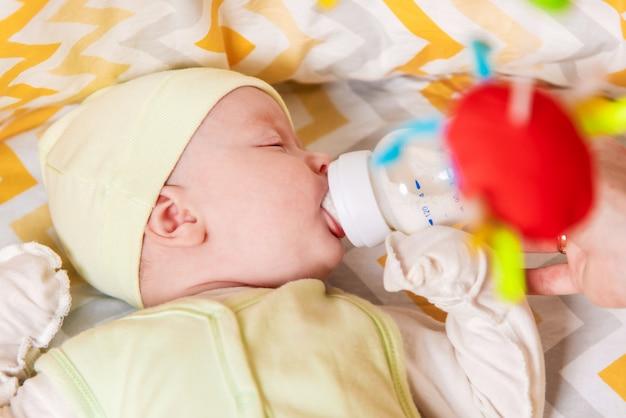 Moeder voedt een pasgeboren baby met melk uit een fles