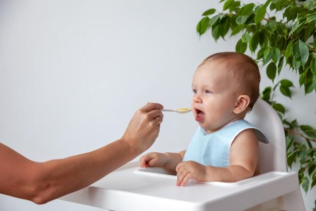 Moeder voedt grappige gelukkige blonde baby in blauwe slabbetje van een lepel