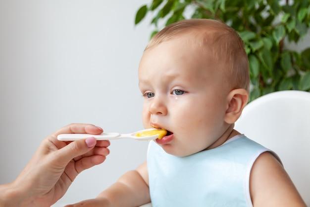 Moeder voedt grappige gelukkige blonde blauwogige baby in blauwe slabbetje van een lepel
