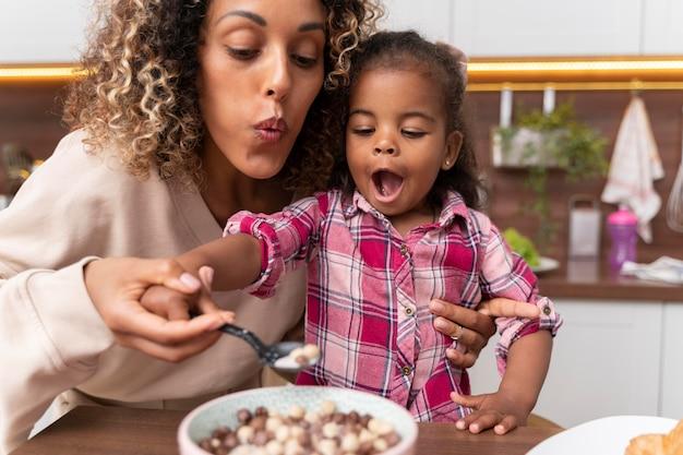 Moeder voedt haar dochter in de keuken