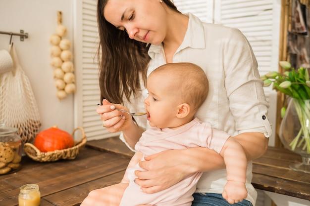 Moeder voedt haar dochter met een lepel in de keuken