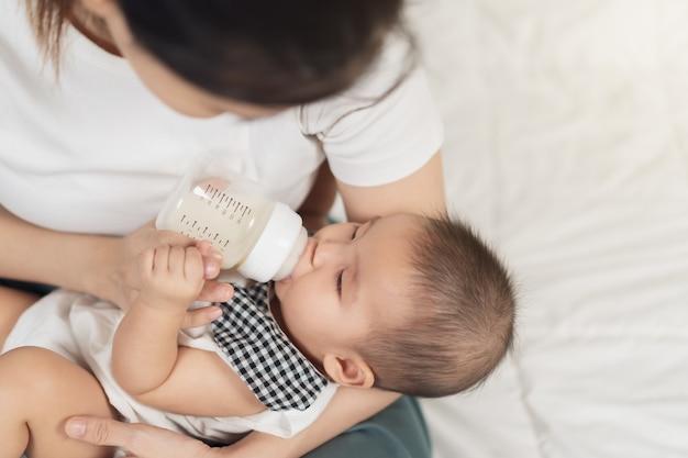 Moeder voedt melk uit de fles en baby slaapt op een bed
