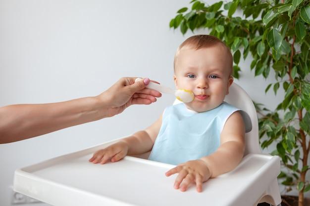 Moeder voedt mooie gelukkige blonde baby in blauwe slabbetje van een lepel