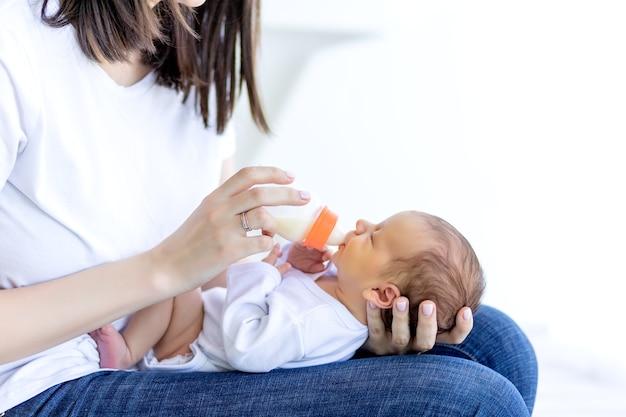 Moeder voedt pasgeboren baby uit een fles