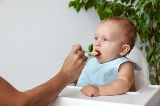 Moeder voedt schattige blonde baby in blauwe slabbetje van een lepel
