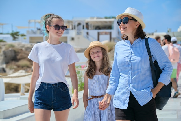 Moeder wandelen met dochters hand in hand in beroemd toeristisch dorp