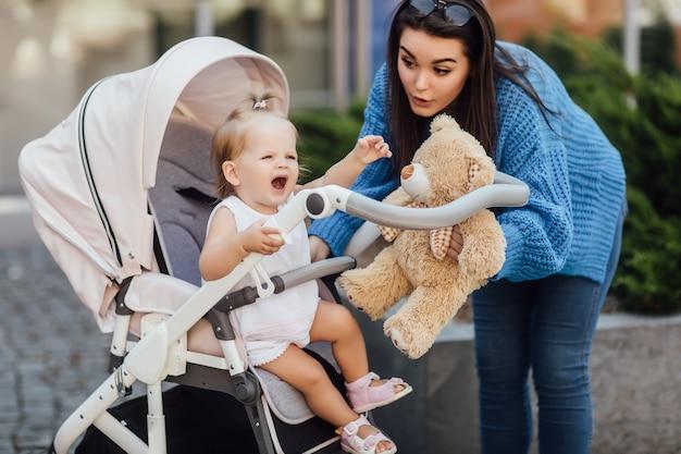 Moeder wandelen met uitgehouwen baby in kinderwagen, vrouw met teddybeer en tijd doorbrengen met haar baby. Premium Foto