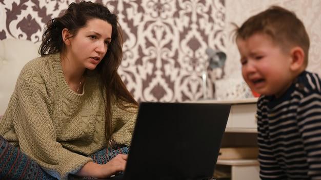 Moeder werkt achter de computer, het kind huilt