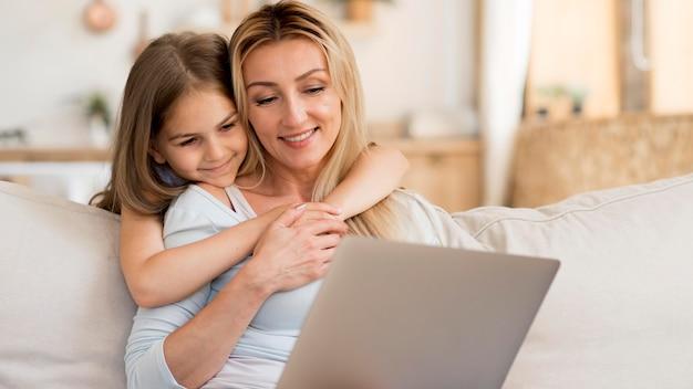 Moeder werkt op laptop vanuit huis met dochter haar omhelzen