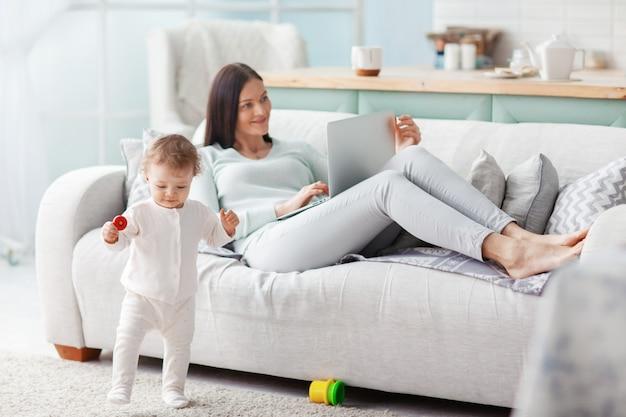 Moeder werkt thuis op een laptop terwijl haar kind aan het spelen is