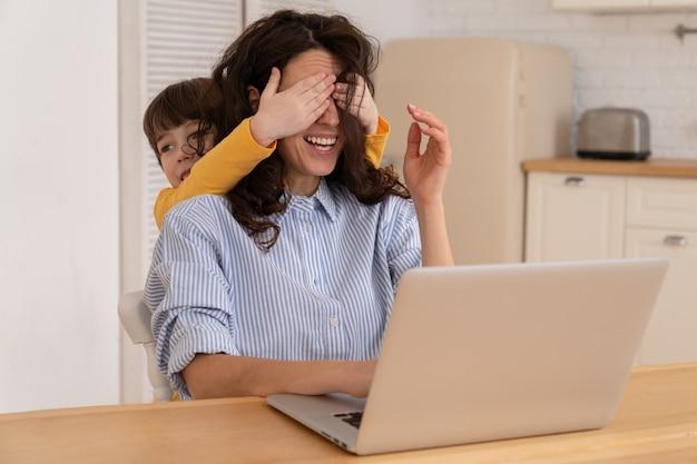 Moeder werkt thuis op laptop tijdens het afsluiten en het kind leidt af, terwijl ze de ogen van haar moeder bedekt