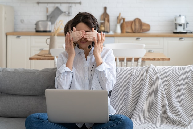 Moeder werkt thuis op laptop tijdens lockdown en kind leidt af van het werk dat de ogen van haar moeder bedekt