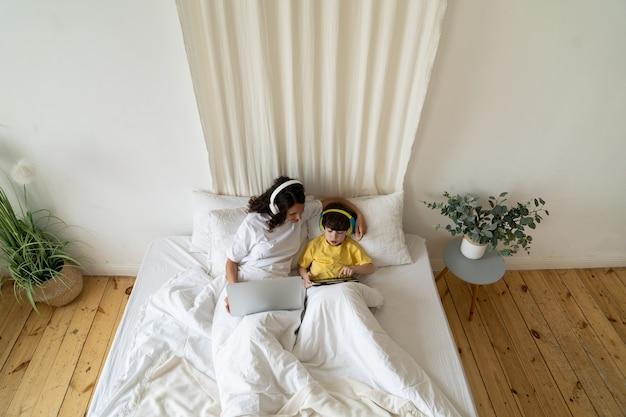 Moeder werkt vanuit huis met coronavirusziekteverlof met kleuterjongen in covid-quarantaine