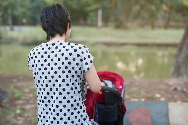 Moeder wiel rode wandelwagen om haar kind te laten daugther om te ontspannen in de zomer park