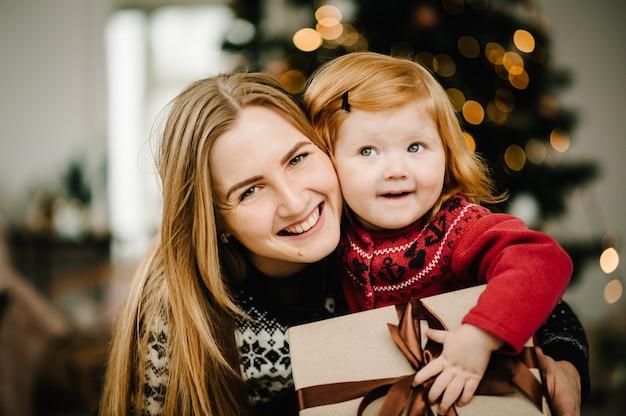 Moeder wisselt geschenken uit met dochter ouder en klein kind hebben plezier bij de kerstboom