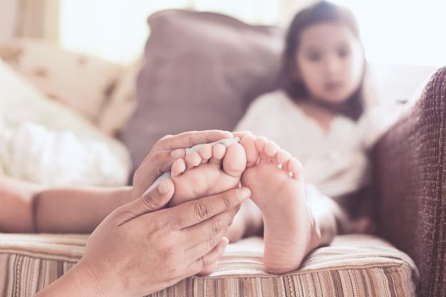 Moeder wrijft over de barefeet van een ziek aziatisch kindmeisje om de koorts met liefde en zorg te verminderen
