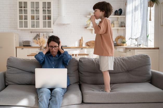 Moeder zakenvrouw werkt vanuit huis bedek oor om te beschermen tegen hyperactief kleuterkind maakt lawaai