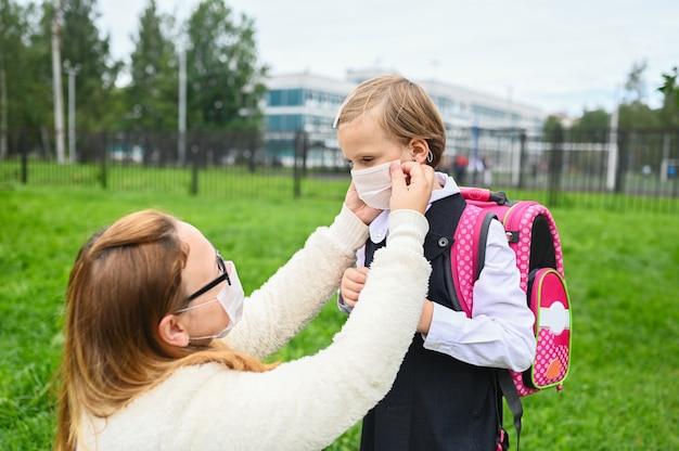 Moeder zet een veiligheidsmasker op het gezicht van haar dochter. schoolmeisje klaar naar school te gaan.