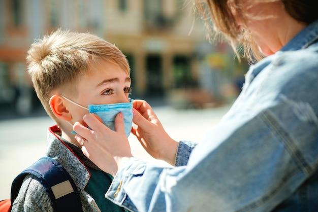 Moeder zet een veiligheidsmasker op het gezicht van haar zoon. schooljongen is klaar om naar school te gaan. terug naar school-concept.