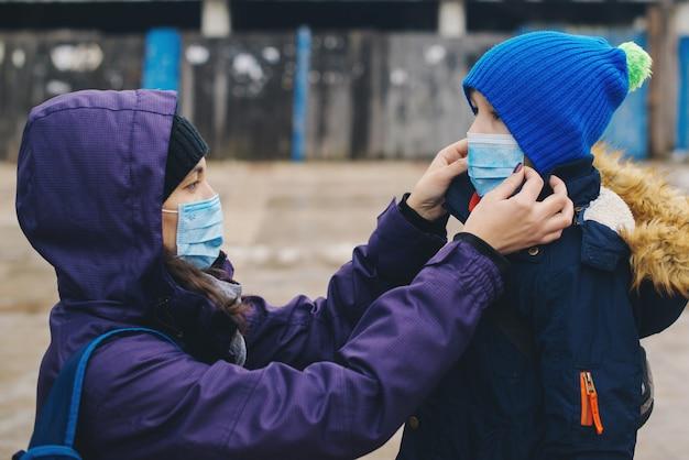 Moeder zet haar kind een gezichtsmasker op straat. stop de infectie. coronavirus-quarantaine. apocalypse.
