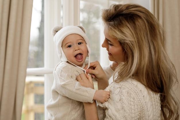 Moeder zette een gebreide muts op haar babyjongen voordat ze naar buiten ging