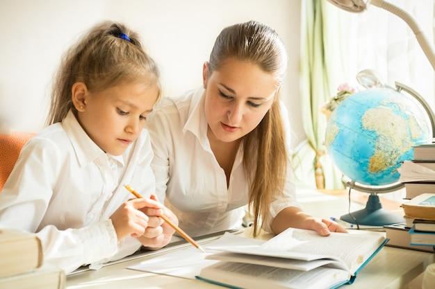Moeder zit met dochter aan bureau en legt ingewikkelde taak uit bij huiswerk