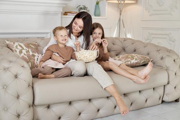 Moeder zit met haar zoon en dochter op de bank en kijkt een film. een vrouw, een jongen en een meisje eten popcorn terwijl ze een film kijken. het gezin rust in het weekend thuis uit
