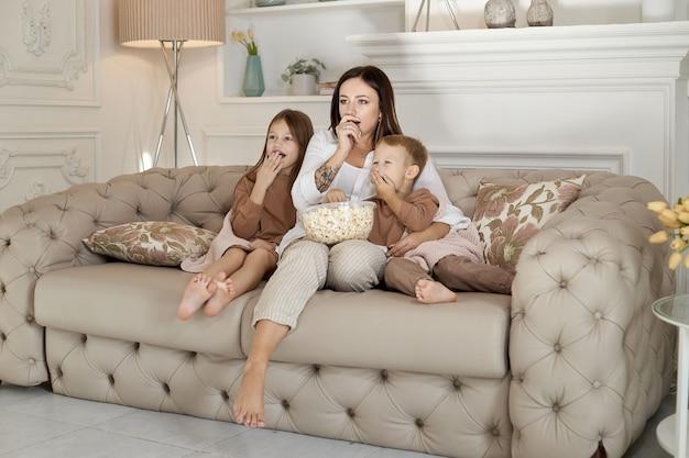 Moeder zit met haar zoon en dochter op de bank en kijkt een film. een vrouw, een jongen en een meisje eten popcorn terwijl ze naar een film kijken. het gezin rust in het weekend thuis uit
