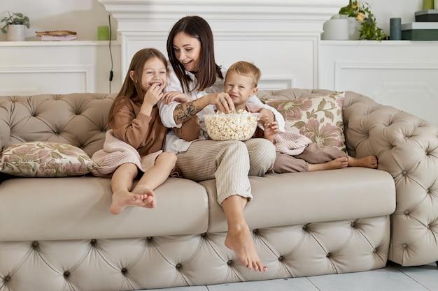 Moeder zit met haar zoon en dochter op de bank en kijkt een film