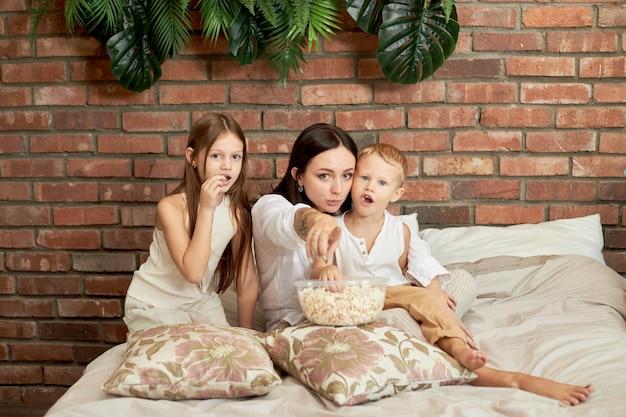 Moeder zit met haar zoon en dochter op het bed en kijkt een film. een vrouw, een jongen en een meisje eten popcorn terwijl ze in de slaapkamer naar een film kijken. het gezin rust in het weekend thuis uit