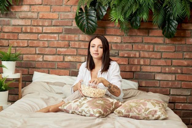 Moeder zit met haar zoon en dochter op het bed en kijkt een film. een vrouw, een jongen en een meisje eten popcorn terwijl ze in de slaapkamer naar een film kijken