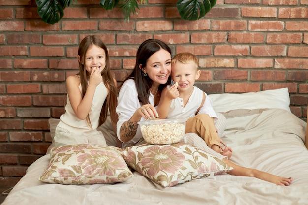 Moeder zit met haar zoon en dochter op het bed en kijkt een film