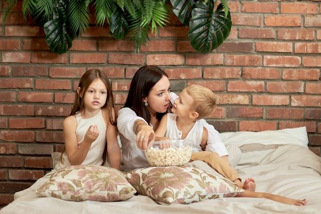 Moeder zit met haar zoon en dochter op het bed en kijkt een film.