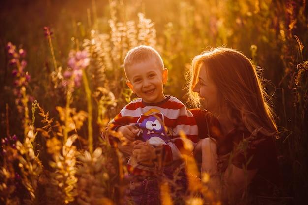 Moeder zit met haar zoon op het veld in de lichten van de avondzon
